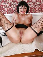 Mature milf Barbie Stroker spreads herself in fence net stockings
